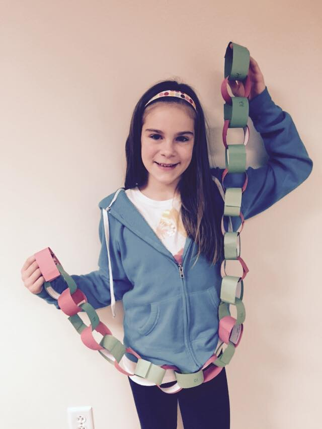 Maria Hopper is holding her paper chain that they  used to countdown their advent calendar.